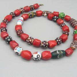 Collarada formada con 23 Perlas de Vidrio de Murano. Son reproducciones de cuentas antiguas y van intercaladas con 24 Coralinas rojas. Están realizadas una a una por un maestro artesano y enfiladas perla-nudo y rematadas con un mosquetón de Plata de Ley